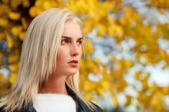 Blonde Frau mit dem langen Haar auf unscharfem natürlichem Herbsthintergrund Stockbilder
