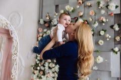 Blonde Frau mit dem langen Haar in einem blauen Kleid küsst leicht ihre kleine Tochter, die sie hält Das Baby mit dem inteer Lizenzfreie Stockfotografie