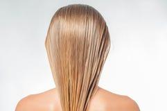 Blonde Frau mit dem langen nassen Haar wendet Pflegespülung an Stockfotos