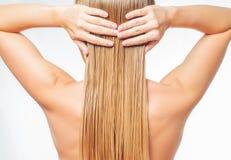 Blonde Frau mit dem langen nassen Haar wendet Pflegespülung an Lizenzfreie Stockfotografie