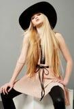 Blonde Frau mit dem langen schönen Haar und den rauchigen Augen in einem Hut Stockfotografie