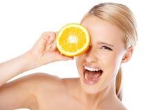 Blonde Frau mit dem schönen Lächeln, das Orange hält Lizenzfreies Stockfoto