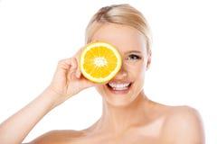 Blonde Frau mit dem schönen Lächeln, das Orange hält Lizenzfreies Stockbild