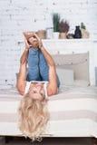 Blonde Frau mit den Beinen oben auf Bett Lizenzfreies Stockbild