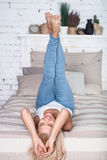 Blonde Frau mit den Beinen oben auf Bett Stockbilder