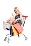 Blonde Frau mit den Beuteln, die in einen Einkaufswagen aufwerfen Stockfotos