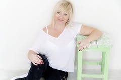 Blonde Frau mit den blauen Augen, die auf dem Boden im leeren Raum sitzen Stockbilder