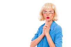 Blonde Frau mit den gefälschten Augen, die Fingerpistole zeigen. Stockfotografie
