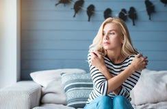 Blonde Frau mit den gekreuzten Armen auf Couch Stockfoto