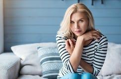 Blonde Frau mit den gekreuzten Armen auf Couch Stockbilder