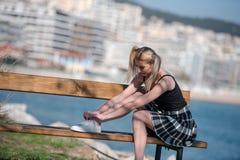 Blonde Frau mit den kleinen Zöpfen, die auf Bank sitzen Stockfotos