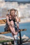 Blonde Frau mit den kleinen Zöpfen, die auf Bank sitzen Lizenzfreie Stockfotografie