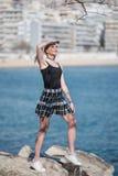 Blonde Frau mit den kleinen Zöpfen, die auf Meer stehen, schaukelt Stockfotografie
