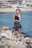 Blonde Frau mit den kleinen Zöpfen, die auf Meer stehen, schaukelt Lizenzfreies Stockfoto