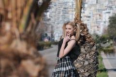 Blonde Frau mit den kleinen Zöpfen, die Minirock tragen, lehnen sich auf Palme Stockfotos