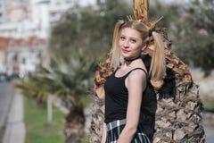 Blonde Frau mit den kleinen Zöpfen, die Minirock tragen, lehnen sich auf Palme Lizenzfreie Stockbilder