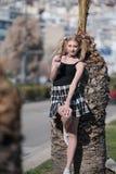 Blonde Frau mit den kleinen Zöpfen, die Minirock tragen, lehnen sich auf Palme Stockfotografie