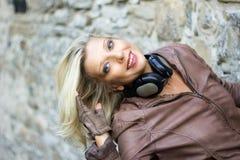 blonde Frau mit den Kopfhörern, die mit ihrem Haar spielen Stockfotos