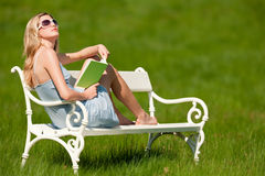 Blonde Frau mit den Sonnenbrillen, die auf weißer Bank sitzen Stockfotos