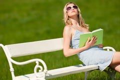 Blonde Frau mit den Sonnenbrillen, die auf weißer Bank sitzen Stockfoto