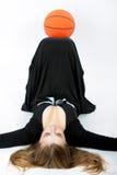Blonde Frau mit der Basketballkugel, die auf Fußboden liegt Stockfotografie