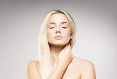 Blonde Frau mit der reinen Haut, die auf grauem Hintergrund aufwirft Stockfotografie