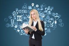 Blonde Frau mit einem Buch nahe einer Geschäftsideenskizze auf einem blauen wa Stockfoto