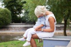 Blonde Frau mit einem Kind auf ihren Knien Stockfoto