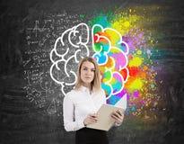 Blonde Frau mit einem Notizbuch nahe einer Tafel mit buntem brai Lizenzfreies Stockfoto