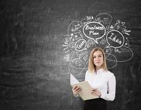 Blonde Frau mit einem Notizbuch nahe einer Tafel mit Unternehmensplan Lizenzfreies Stockbild