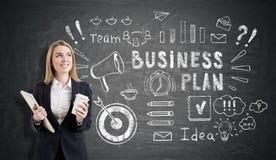 Blonde Frau mit einem Notizbuch und ein Tasse Kaffee und ein Geschäft p Lizenzfreie Stockfotos