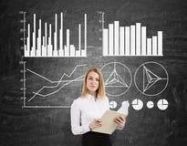 Blonde Frau mit einem Notizbuch und vier Diagramme auf einer Tafel Stockbild