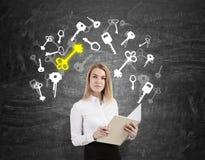Blonde Frau mit einem Notizbuch und weißen und gelben Schlüsseln Stockfoto