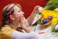 Blonde Frau mit einem Osterei denkt Stockfotos