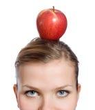 Blonde Frau mit einem roten Apfel auf ihrem Kopf Lizenzfreie Stockbilder