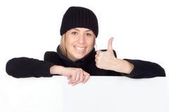 Blonde Frau mit einem schwarzen Mantel o.k. sagend Lizenzfreies Stockfoto
