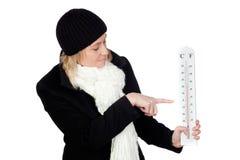 Blonde Frau mit einem schwarzen Mantel und einem Thermometer Stockbilder