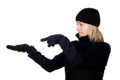 Blonde Frau mit einem schwarzen Mantelzeigen Lizenzfreies Stockfoto