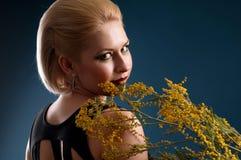 Blonde Frau mit einem Zweig Stockfoto