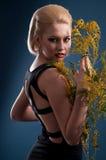 Blonde Frau mit einem Zweig Stockfotografie