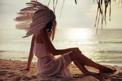 Blonde Frau mit einer enormen Feder den Sonnenuntergang aufpassend Lizenzfreie Stockbilder