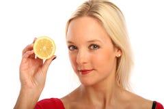 Blonde Frau mit einer halben Zitrone Stockbild