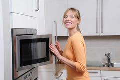 Blonde Frau mit einer Mikrowelle Stockfotografie