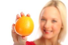 Blonde Frau mit einer Orange Stockbild