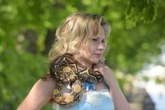 Blonde Frau mit einer Pythonschlange in den Händen Lizenzfreie Stockfotos