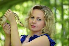 Blonde Frau mit einer Pythonschlange in den Händen Stockbild
