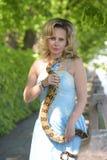 Blonde Frau mit einer Pythonschlange in den Händen Stockfotografie