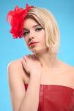 Blonde Frau mit einer roten Blume im Haar Stockfotos
