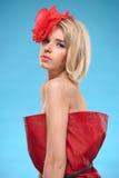 Blonde Frau mit einer roten Blume im Haar Stockfotografie