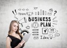 Blonde Frau mit einer Spaltung und einem Unternehmensplan Lizenzfreie Stockfotos